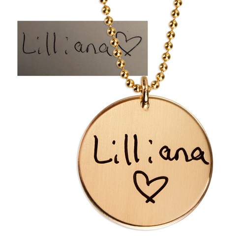 """Custom gold disc handwriting necklace, personalized with daughter's handwritten signature """"Lilliana (heart)"""", shown close up on white"""