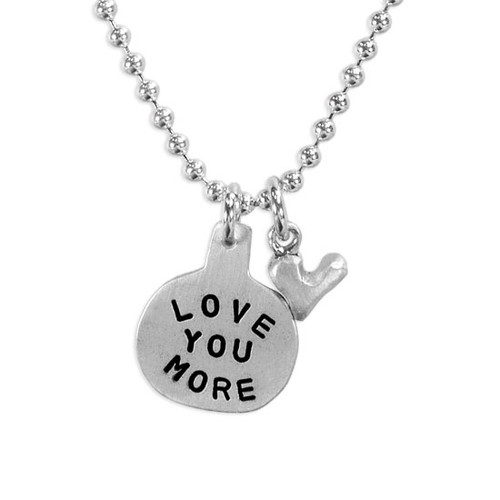 Silver necklace Hand Stamped with the words Love You More , and a silver heart charm, shown on white, close up