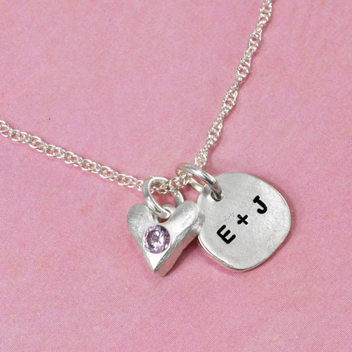 Sculpted Nugget round fine silver charm with initials with fine silver handmade heart with embedded birthstone on pink background
