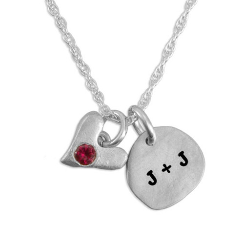 Close up image of Sculpted Nugget round fine silver charm with initials with fine silver handmade heart with embedded birthstone on white background