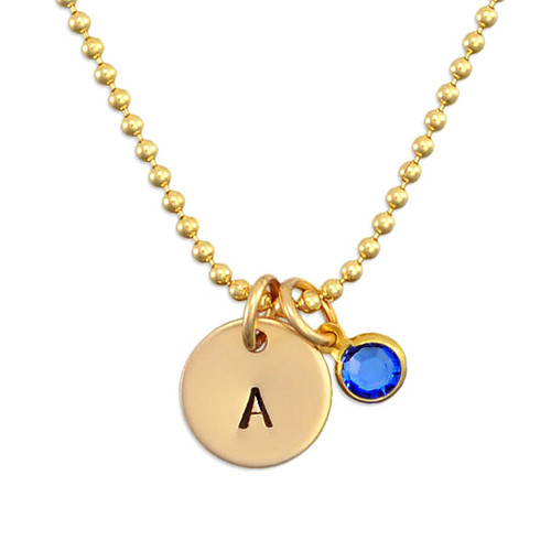 Custom Hand Stamped Gold initial birthstone necklace, personalized with child's initial & blue birthstone, shown close up on white