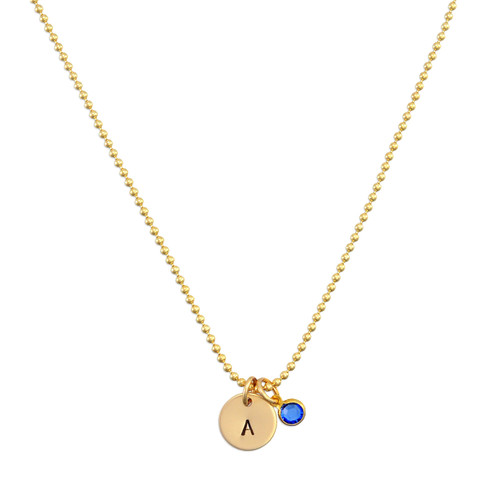 Custom Hand Stamped Gold initial birthstone necklace, personalized with child's initial & blue birthstone, shown on white