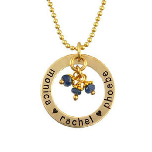 Gold custom hand stamped circle necklace personalized with kids names and birthstones, shown on white
