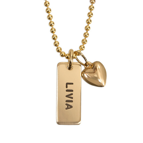 """Custom personalized gold necklace with rectangle charm for mom, hand stamped with child's name """"Livia"""", with a puffed gold heart charm, shown close up on white"""