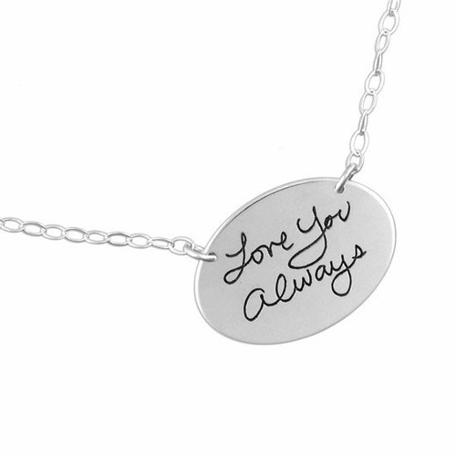 Silver oval charm necklace with actual handwriting, on a silver flat cable chain, shown close up