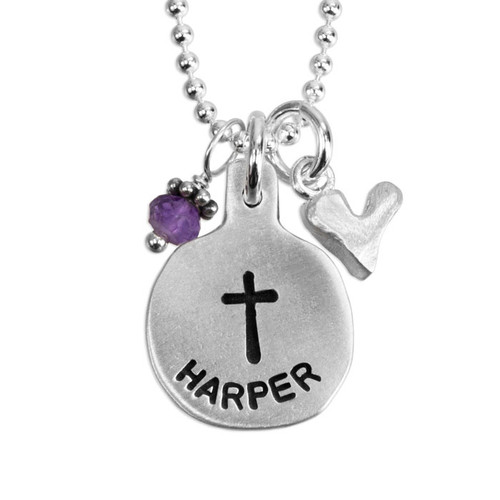 """close up view of custom silver necklace for first communion, stamped with the name """"Harper"""", with silver heart charm and purple birthstone, shown on white"""