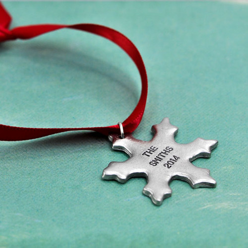 Custom Hand stamped fine pewter snowflake ornament, personalized with your message, shown on green
