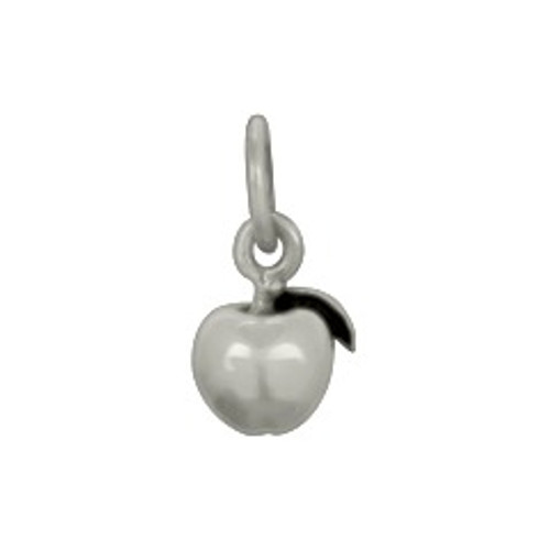 Tiny sterling silver apple charm for teachers, shown close up on white
