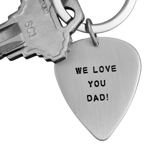 Close up of sterling silver hand stamped guitar pick key chain shown with key on white background