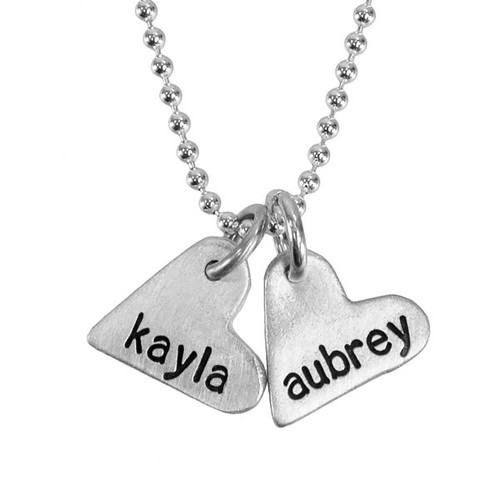 handcrafted silver heart charm necklace, hand stamped with names, shown up close on white