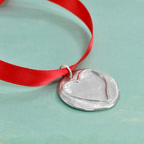 Front side of the Love You Handwritten Christmas Tree Ornament, featuring a hand sculpted fine pewter disc with a raised outline of a heart, hung on a red ribbon. Shown from the side on green background