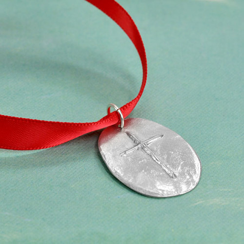 Front of custom fine pewter Cross Ornament, featuring a raised cross on a hand sculpted oval, hung on a red ribbon, shown from the side on a green background.