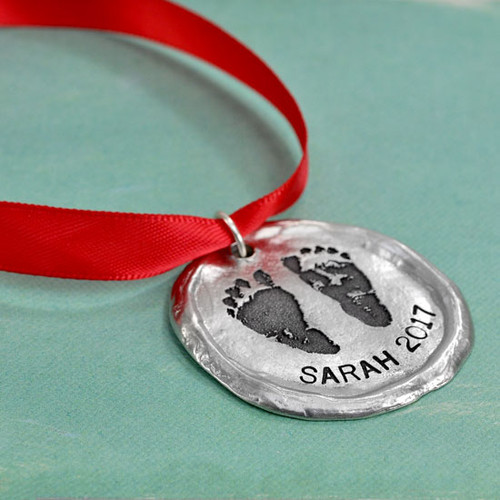 Custom fine pewter memorial Christmas ornament, personalized with your child's footprints or handprints, shown on green