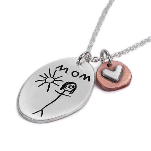 Side view of handmade sterling silver oval custom engraved with child's drawing of Mom and the sun. Paired with copper disc with silver raised heart, hung on a silver ball chain.