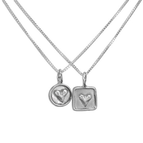 Personalized silver heart necklaces, one with a raised heart on a silver circle frame, the other with a raised heart on a silver square frame. Both necklaces shown on white background.