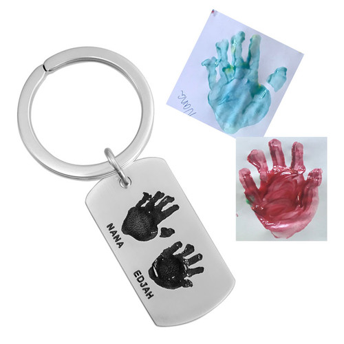 Custom silver key ring gift for Dad with kids actual handprint engraved on the front, with their names stamped below, shown with the original painted handprints used to personalize they key chain