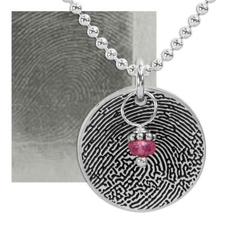 Custom sterling silver disc fingerprint necklace engraved with your actual fingerprint, with a red birthstone, shown with the original fingerprint used to personalize it
