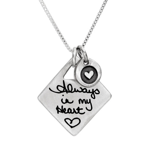 Loved one's handwritten note custom engraved on a personalized diamond shaped silver charm, with silver heart charm, shown close up on white