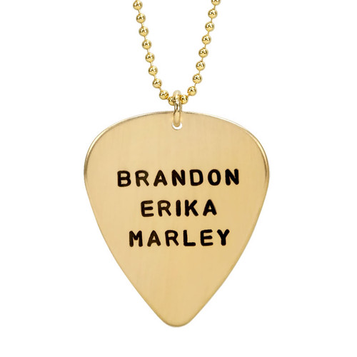 hand stamped personalized guitar pick in gold, shown up close on white