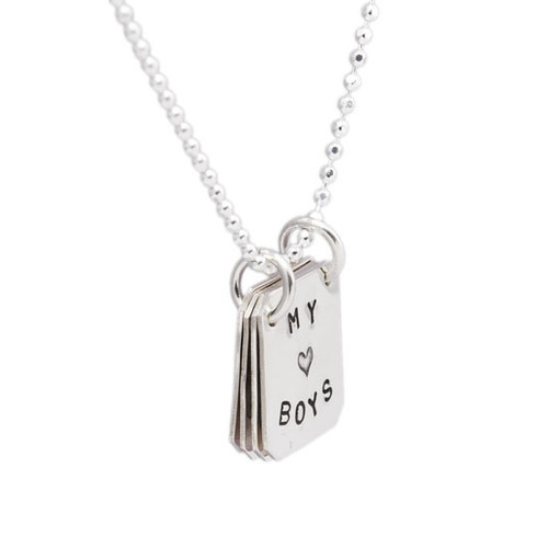Book Of Love silver hand stamped personalized necklace, shown close up on white