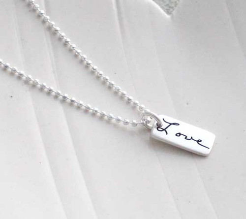 "Dainty Custom SIlver Handwriting Tag necklace, personalized with loved one's handwritten word ""Love"", shown from the side"