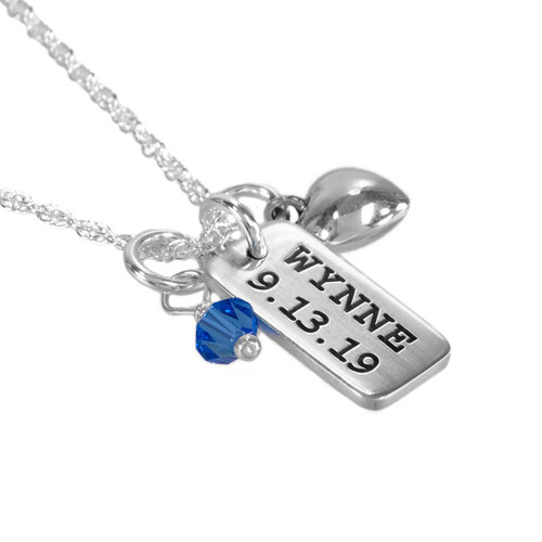 Hand stamped silver Dainty Rectangle personalized with child's name and birthday, hung with birthstone and puffed silver heart on silver chain, shown from the side