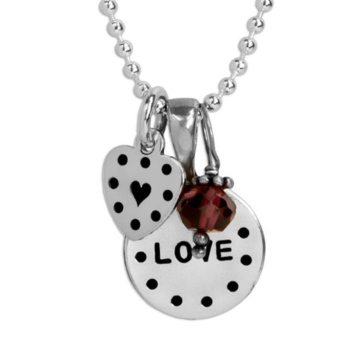 Personalized silver disc and silver heart necklace, hand stamped with dotted border and the word love, with a garnet birthstone, shown close up on white