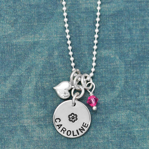 Silver Girls Disc with Heart and Birthstone, hand stamped with a flower and girl's name, show close up on green