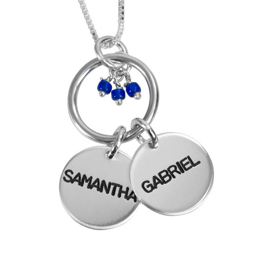 Close up view of custom Hollow Circle Name Necklace, personalized with kids' names Samantha & Gabriel, stamped on 2 silver discs, hung on a silver ring and with a dark blue stone cluster of 3 stones, shown on white