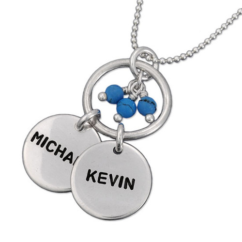 Custom Hollow Circle Name Necklace, personalized with kids' names stamped on 2 silver discs, hung on a silver ring and with blue stone cluster, shown on white