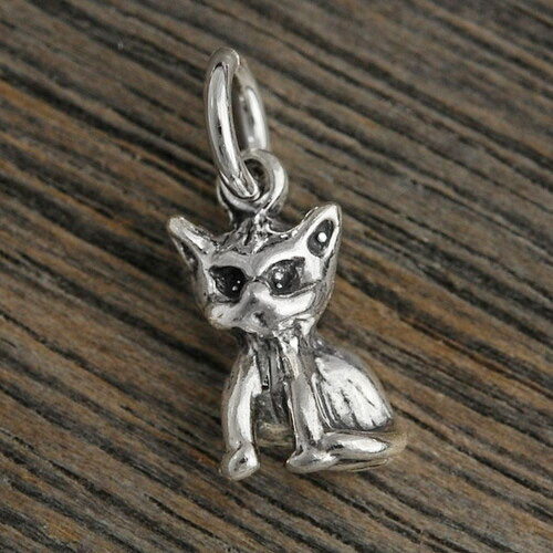 Sterling silver Little 3D Kitty Charm that can be added to a necklace or bracelet, shown on wood background