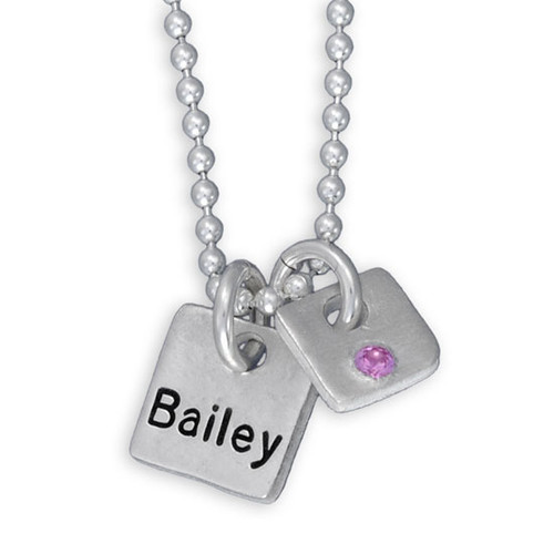 Fine silver Mini Squares personalized necklace, hand stamped with kid's name and with an embedded birthstone, shown close up on white