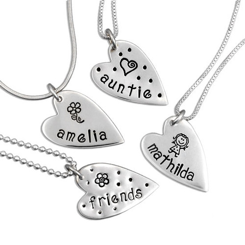 Custom Hand stamped mommy jewelry, with sterling silver hearts personalized with names, shown on white