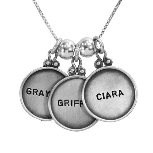 Personalized vintage style sterling silver circles with raised edges, hand stamped with kids names , shown close up on white