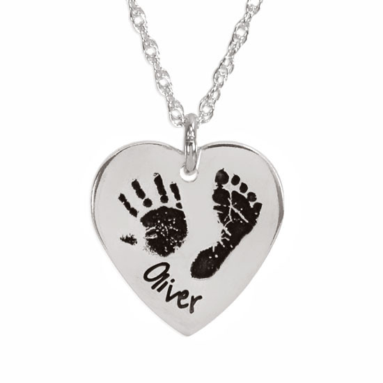 Actual child's handprint and footprint custom engraved on a silver heart charm on a personalized silver necklace, shown close up on white