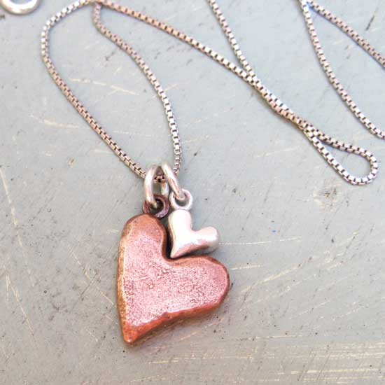 Hand sculpted copper and silver hearts nested together on a silver chain, shown from the top