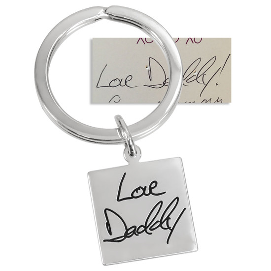Sterling silver key ring with handwriting etched into the charm, shown with original handwritten note used to create it