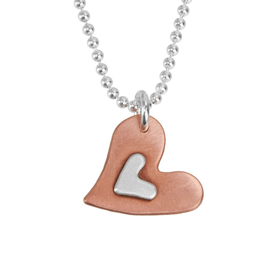 Handmade Subtle Devotion necklace with copper heart and silver heart in the middle, shown close up on white