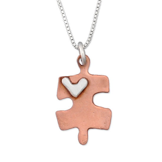 Handmade copper puzzle piece charm with silver heart on a necklace, shown close up on white