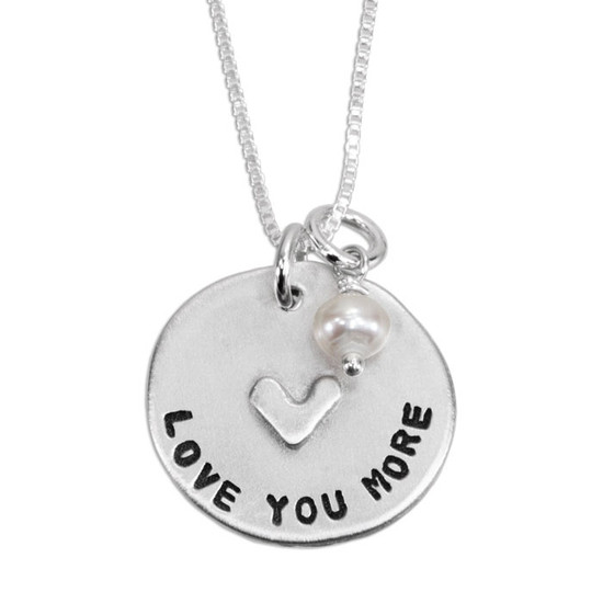 """Close up of custom hand stamped mom necklace in fine pewter, shown with pearl, personalized with the message, """"Love You More"""""""
