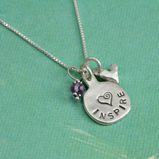 Silver necklace hand stamped with the word Inspire and a heart, with a birthstone and a silver heart charm hung on a silver chain