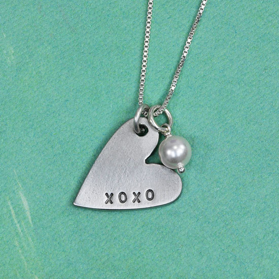 Custom hand stamped XOXO Heart Necklace, with Swarovski Pearl, shown close up on green