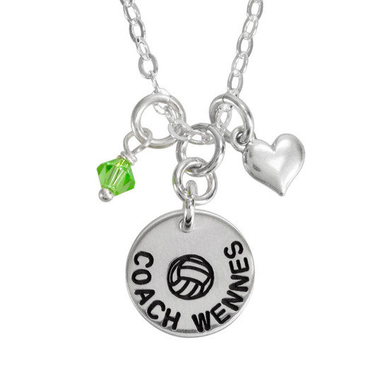 Custom silver circle charm necklace for a coach or athlete, personalized with symbol of the sport and the coach's name, along with a team color birthstone and silver puffed heart charm. Shown close up on white background