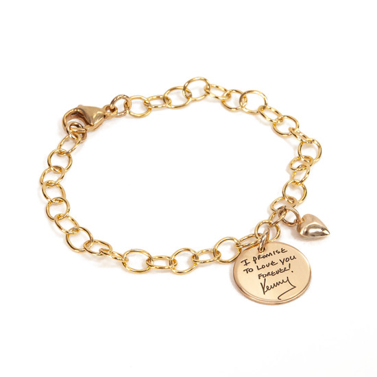Personalized gold charm bracelet, custom engraved with note in husband's handwriting, with round disc charm & gold puffed heart, shown from the side on white