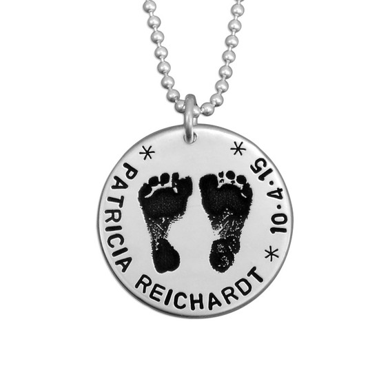 Sterling silver custom footprint necklace with your child's footprints, hand stamped with names and date, shown close up on white