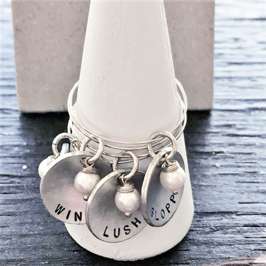 Custom hand stamped wine glass charms in sterling silver personalized with names or words