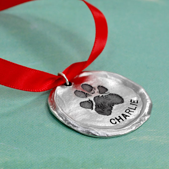 Custom fine pewter Christmas ornament, personalized with your dog or cat's pawprint, shown close up on green