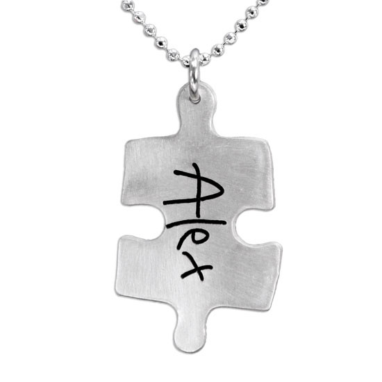 Silver Puzzle necklace with child's handwritten name, shown close up