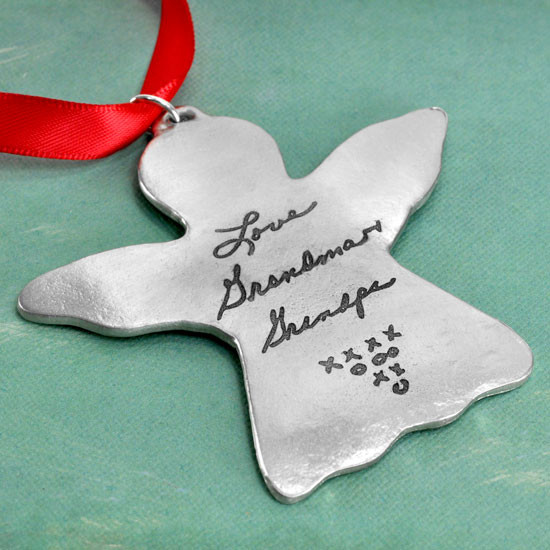 Handwriting Angel Ornament in fine pewter, made with your loved one's actual handwriting, with red ribbon, shown close up on green