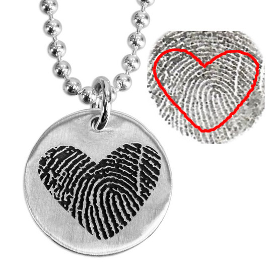 Custom Silver fingerprint necklace, personalized with loved one's actual fingerprint, shown close up on white, with the original fingerprint used to personalize it, highlighted to show where the print cut out came from